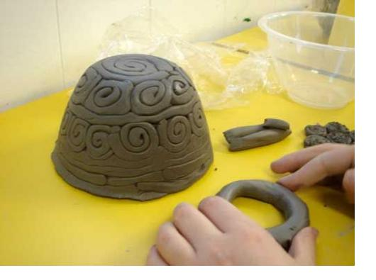 Pictured: Child's hand pressing on clay in front of small bowl with textured swirls